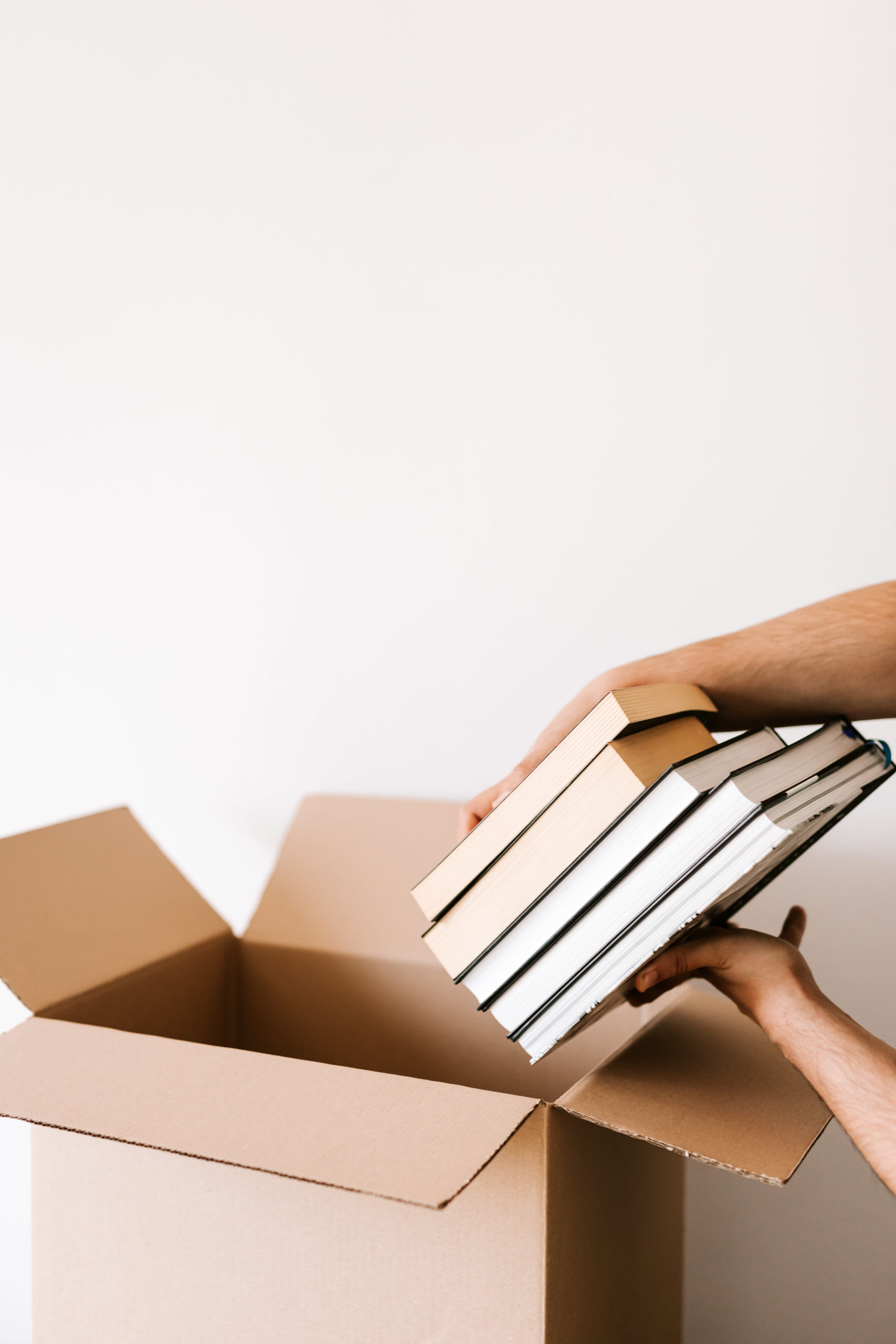 crop person packing stack of books in carton box 4498137 scaled