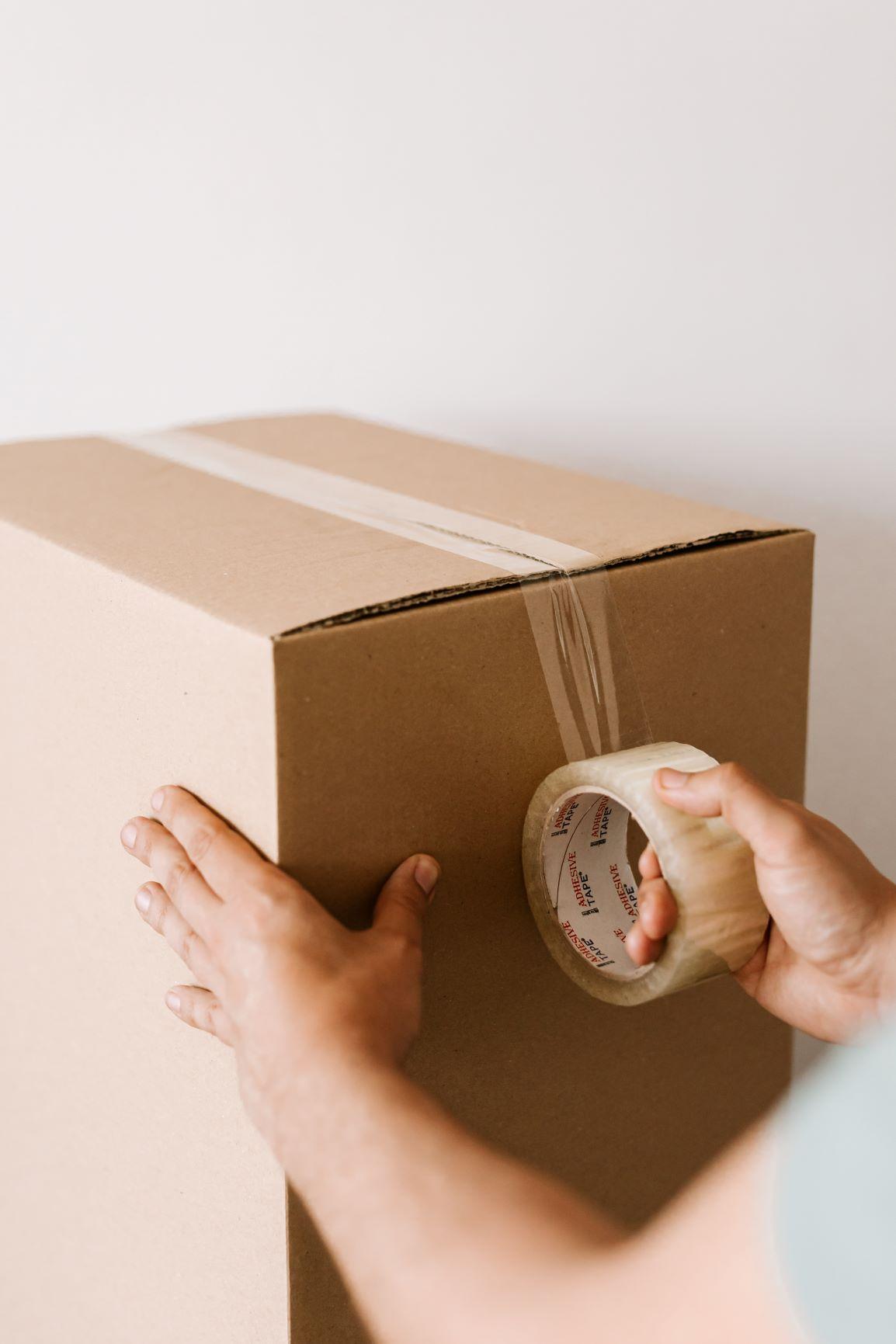 man sealing moving box with tape 2